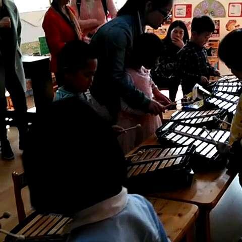 泸州天立学校附属幼儿园何老师辅导小朋友们练习小钟琴.